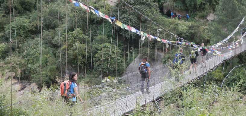 Trekkers crossing river through suspension bridge